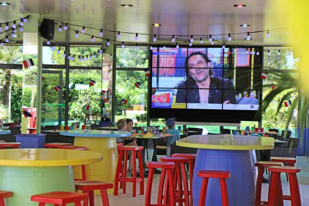 Une belle salle, avec tables, mange-debout et écran géant